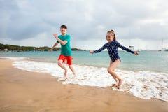 Kids having fun at beach. Kids brother and sister at tropical beach during summer vacation stock photos