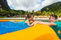 Kids having fun at beach. Kids having fun at tropical beach during summer vacation playing together at shallow water royalty free stock photo