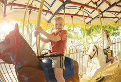 Kids having fun on a Carnival Carousel. Two cute kids having fun while riding a carousel at an amusement park or carnival Stock Photo