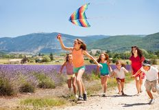 Kids having fun flying colorful kite in summer stock photography