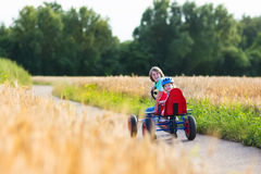 Kids having fun with a go cart car. Two happy children, laughing boy and his funny little sister, adorable toddler girl, playing together enjoying a go cart car Stock Photos