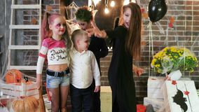Kids having fun at halloween party, harley quinn and joker, party of evil, halloween celebration stock footage
