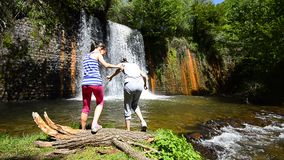 Kids having fun near waterfall stock footage