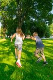 Kids having fun in the park, run and play. Sister and brother having fun in the park, run and play. They are happy royalty free stock image