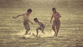 Kids are having fun playing football in the field. royalty free stock image