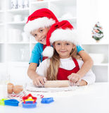 Kids having fun preparing christmas cookies. Stretching the dough Stock Photos