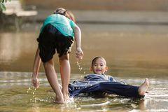 Kids having fun in puddle Stock Image