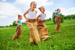 Kids having fun with sacks on a meadow Royalty Free Stock Image
