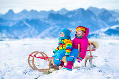 Kids having fun on a sleigh ride in snow Royalty Free Stock Photography