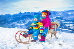 Kids having fun on a sleigh ride in snow Stock Photo