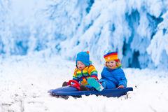 Kids having fun on a sleigh ride in winter. Little girl and boy enjoy a sleigh ride. Child sledding. Toddler kid riding a sledge. Children play outdoors in snow Royalty Free Stock Image