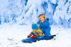 Kids having fun on a sleigh ride in winter Stock Photography