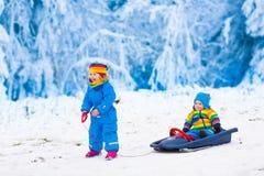 Kids having fun on a sleigh ride in winter Stock Photo