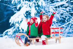 Kids having fun on a sleigh ride in winter. Little girl and boy enjoy a sleigh ride. Child sledding. Toddler kid riding a sledge. Children play outdoors in snow Stock Photo