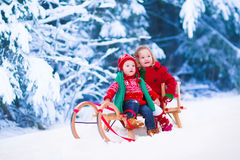 Kids having fun on a sleigh ride in winter Stock Images