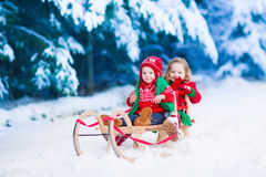 Kids having fun on a sleigh ride in winter Stock Photo