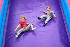 Kids Having Fun on Slide. Young Children on Bouncy Castle Slide Royalty Free Stock Photos
