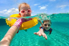 Kids having fun swimming on summer vacation. Split above and underwater photo of adorable kids having fun swimming on summer vacation Stock Image