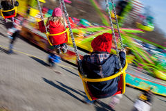 Kids, having fun on a swing chain carousel ride. Motion blur Stock Images