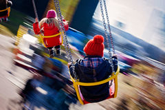 Kids, having fun on a swing chain carousel ride. Motion blur Royalty Free Stock Images