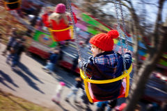 Kids, having fun on a swing chain carousel ride. Motion blur Royalty Free Stock Photos