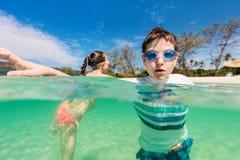Kids having fun at beach. Kids having fun at tropical beach during  summer vacation playing together at shallow water Stock Images