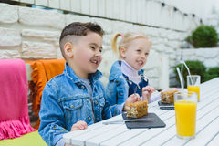 Kids having healthy breakfast. children drinking juice and eating pie Royalty Free Stock Photo