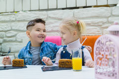 Kids having healthy breakfast. children drinking juice and eating pie Stock Photo