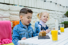 Kids having healthy breakfast. children drinking juice and eating pie Stock Photos