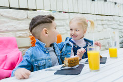 Kids having healthy breakfast. children drinking juice and eating pie Stock Images