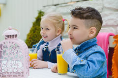 Kids having healthy breakfast. children Drinking juices and have fun Stock Photo