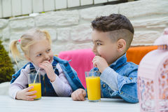 Kids having healthy breakfast. children Drinking juices and have fun Royalty Free Stock Images