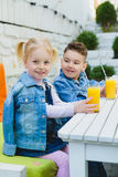 Kids having healthy breakfast. children Drinking juices and have fun Stock Image
