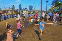 Kids having a lot of fun playing with colourful soap bubbles on the Thames bankside near the Millennium Bridge in London. stock image