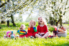 Kids having picnic in blooming garden. Little children eating lunch outdoors. Kids with picnic basket in spring garden with blooming apple and cherry tree Stock Image