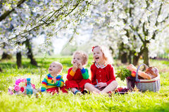 Kids having picnic in blooming garden. Little children eating lunch outdoors. Kids with picnic basket in spring garden with blooming apple and cherry tree Royalty Free Stock Image