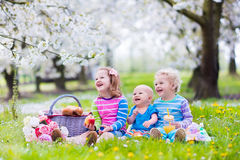 Kids having picnic in blooming garden Stock Images