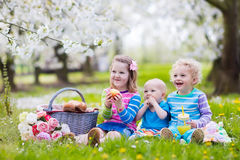 Kids having picnic in blooming garden. Little children eating lunch outdoors. Kids with picnic basket in spring garden with blooming apple and cherry tree Royalty Free Stock Images