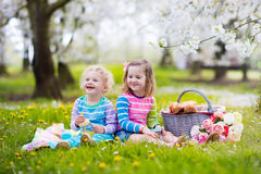 Kids having picnic in blooming garden. Little children eating lunch outdoors. Kids with picnic basket in spring garden with blooming apple and cherry tree Royalty Free Stock Photography
