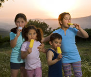 Kids having pop ice. Four kids having pop ice in a summer sunset Stock Photo