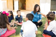 Kids having a preschool class outdoors. Group of preschool pupils enjoying a class with their teacher outdoors and sitting on the grass royalty free stock photo