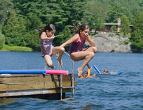 Kids having summer fun  jumping off dock into lake. Kids having summer fun jumping off the dock into clear lake holding their noises Stock Photo