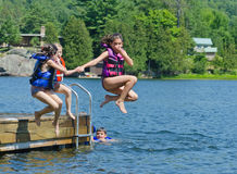 Kids having summer fun  jumping off dock into lake. Kids having summer fun jumping off the dock into clear lake with life-jackets on Royalty Free Stock Image