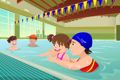 Kids having a swimming lesson in indoor pool Royalty Free Stock Photos