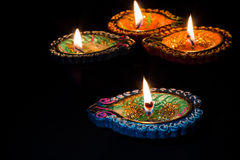Four burning colorful candles indian style for Diwali celebration. Black background. Stock Photos
