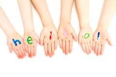 Kids hello welcome painted on hands. Kids hands with hello welcome painted on them. On white Royalty Free Stock Photos
