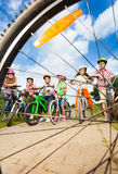 Kids with helmets hold bikes view through spoke Royalty Free Stock Photo