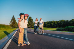 Kids in helmets. Little girl and boy in helmets hugging each other and grandparents with bicycle standing behind Royalty Free Stock Photography