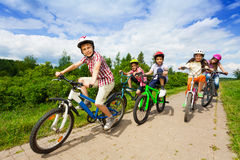 Kids in helmets riding bikes together stock photography