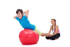 Kids helping each other exercising with a large gymnastic rubber Stock Image